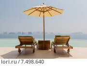 Купить «infinity pool with parasol and sun beds at seaside», фото № 7498640, снято 15 февраля 2015 г. (c) Syda Productions / Фотобанк Лори