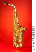 Купить «Альт-саксофон на красном фоне», фото № 7499864, снято 23 февраля 2015 г. (c) Сергей Новиков / Фотобанк Лори