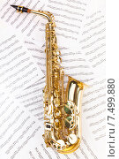 Купить «Блестящий золотой саксофон лежит на нотных листах», фото № 7499880, снято 23 февраля 2015 г. (c) Сергей Новиков / Фотобанк Лори