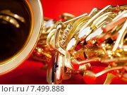 Купить «Крупным планом вид саксофона на красном фоне», фото № 7499888, снято 23 февраля 2015 г. (c) Сергей Новиков / Фотобанк Лори
