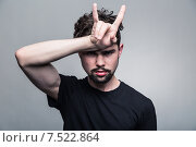 """Купить «Молодой мужчина с усами и бородой показывает рукой жест """"коза"""" на сером фоне», фото № 7522864, снято 30 апреля 2015 г. (c) Константин Колосов / Фотобанк Лори"""