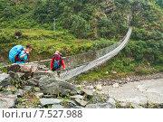 Девушка туристка переходит реку Кали Гандаки по подвесному мосту в сопровождении непальского гида (2012 год). Редакционное фото, фотограф Юлия Бабкина / Фотобанк Лори