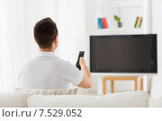 Купить «man watching tv and changing channels at home», фото № 7529052, снято 29 января 2015 г. (c) Syda Productions / Фотобанк Лори