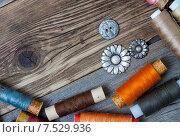 Купить «Пуговицы и катушки ниток на деревянном столе», фото № 7529936, снято 1 июня 2015 г. (c) Astroid / Фотобанк Лори