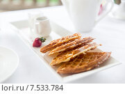 Купить «close up of waffles on plate at breakfast table», фото № 7533784, снято 23 февраля 2015 г. (c) Syda Productions / Фотобанк Лори
