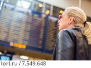 Девушка ищет рейс в расписании на табло в аэропорту. Стоковое фото, фотограф Matej Kastelic / Фотобанк Лори