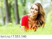 Купить «Красивая улыбчивая девушка в красной кофточке лежит на траве в парке», фото № 7551140, снято 3 июня 2015 г. (c) Иван Михайлов / Фотобанк Лори