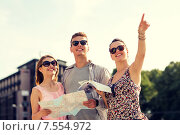 Купить «smiling friends with map and city guide outdoors», фото № 7554972, снято 20 июля 2014 г. (c) Syda Productions / Фотобанк Лори