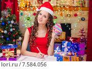 Купить «Красивая девушка составляет список новогодних подарков», фото № 7584056, снято 3 декабря 2014 г. (c) Иванов Алексей / Фотобанк Лори