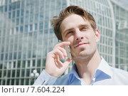Молодой привлекательный мужчина разговаривает по телефону на фоне современного здания. Стоковое фото, фотограф Дмитрий Булин / Фотобанк Лори