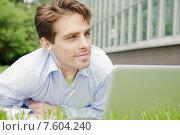 Купить «Молодой мужчина с ноутбуком и наушниками лежит на траве», фото № 7604240, снято 9 июня 2015 г. (c) Дмитрий Булин / Фотобанк Лори