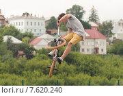 Парень совершает прыжок с трамплина на велосипеде с исполнением трюка на фестивале Экшен спорт в городе Ельце Липецкой области (2015 год). Редакционное фото, фотограф Игорь Хамицаев / Фотобанк Лори