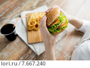 Купить «close up of woman hands holding hamburger», фото № 7667240, снято 21 мая 2015 г. (c) Syda Productions / Фотобанк Лори