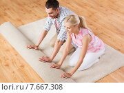 Купить «happy couple unrolling carpet or rug at home», фото № 7667308, снято 6 июня 2015 г. (c) Syda Productions / Фотобанк Лори