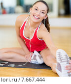 Купить «smiling girl with smartphone and earphones in gym», фото № 7667444, снято 28 сентября 2013 г. (c) Syda Productions / Фотобанк Лори