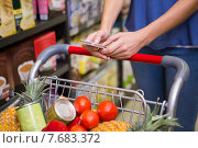 Купить «Pretty woman pushing trolley in aisle and texting», фото № 7683372, снято 21 января 2015 г. (c) Wavebreak Media / Фотобанк Лори