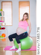 Купить «Pregnant woman looking at camera sitting on exercise ball», фото № 7683716, снято 21 апреля 2015 г. (c) Wavebreak Media / Фотобанк Лори