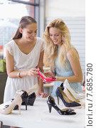 Купить «Two happy women looking at heel shoe», фото № 7685780, снято 3 марта 2015 г. (c) Wavebreak Media / Фотобанк Лори