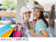 Купить «Happy women smiling at camera with shopping bags», фото № 7686412, снято 3 марта 2015 г. (c) Wavebreak Media / Фотобанк Лори