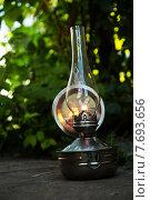 Зажженная Старая керосиновая лампа стоит на земле в зарослях. Стоковое фото, фотограф Владимир Ходатаев / Фотобанк Лори