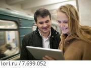 Купить «Молодая пара с планшетом в руках стоит на перроне станции метро», фото № 7699052, снято 13 марта 2015 г. (c) Данил Руденко / Фотобанк Лори