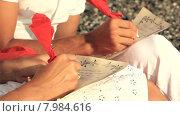 Купить «Молодой мужчина и женщина пишут романтические письма», видеоролик № 7984616, снято 18 июня 2015 г. (c) Tatiana Kravchenko / Фотобанк Лори