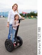 Купить «Счастливая молодая женщина и ее дочь на сегвее», фото № 8127180, снято 26 мая 2019 г. (c) Дарья Петренко / Фотобанк Лори