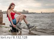 Молодая девушка в роликах сидит на набережной у самой воды. Санкт-Петербург (2015 год). Стоковое фото, фотограф Ивашков Александр / Фотобанк Лори