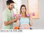 Купить «Pregnant woman sitting on exercise ball and lifting dumbbells», фото № 8193288, снято 23 апреля 2015 г. (c) Wavebreak Media / Фотобанк Лори