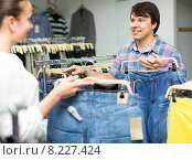 Купить «Positive couple buying jeans in shop», фото № 8227424, снято 22 августа 2018 г. (c) Яков Филимонов / Фотобанк Лори