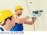 Купить «group of builders with drill indoors», фото № 8378428, снято 25 сентября 2014 г. (c) Syda Productions / Фотобанк Лори