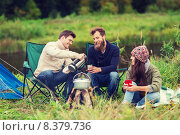 Купить «group of smiling tourists cooking food in camping», фото № 8379736, снято 31 августа 2014 г. (c) Syda Productions / Фотобанк Лори