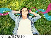 Купить «smiling young girl in headphones lying on grass», фото № 8379944, снято 11 июля 2014 г. (c) Syda Productions / Фотобанк Лори