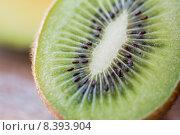 Купить «close up of ripe kiwi slice on table», фото № 8393904, снято 17 марта 2015 г. (c) Syda Productions / Фотобанк Лори