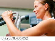 Купить «Woman in gym on machine exercising», фото № 8430052, снято 19 июля 2019 г. (c) PantherMedia / Фотобанк Лори