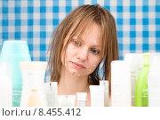 Купить «Девушка смотрит на косметические средства», фото № 8455412, снято 26 июня 2015 г. (c) Andrei Korzhyts / Фотобанк Лори