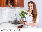 Купить «Домохозяйка стоит на кухне и держит в руках горшок с кустовой декоративной розой», фото № 8461136, снято 27 июля 2015 г. (c) Кекяляйнен Андрей / Фотобанк Лори