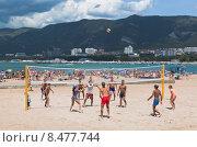 Купить «Молодые люди играют в волейбол на песчаном пляже города курорта Геленджика», фото № 8477744, снято 13 июля 2015 г. (c) Николай Мухорин / Фотобанк Лори