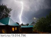 Купить «Сильный и мощный удар молнии над домами в деревне ночью», фото № 9014796, снято 2 июня 2015 г. (c) Михаил Дударев / Фотобанк Лори