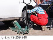 Купить «Мастер шиномонтажа устанавливает переднее колесо на автомобиль», фото № 9259940, снято 11 апреля 2015 г. (c) Manapova Ekaterina / Фотобанк Лори
