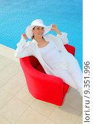 Купить «Beautiful woman relaxing in red chair by a swimming-pool», фото № 9351996, снято 19 сентября 2019 г. (c) PantherMedia / Фотобанк Лори