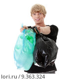 Купить «Young man carrying a plastic trash bags full with empty recyclable household material.», фото № 9363324, снято 17 декабря 2018 г. (c) PantherMedia / Фотобанк Лори