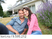 Купить «Portrait of happy couple sitting in front of their new house», фото № 9595212, снято 21 сентября 2018 г. (c) PantherMedia / Фотобанк Лори