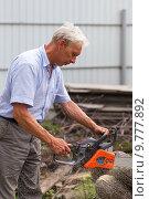 Купить «Мужчина пилит бревна с помощью бензопилы. Фокус на руке», фото № 9777892, снято 30 июня 2015 г. (c) Евгений Ткачёв / Фотобанк Лори