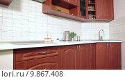 Интерьер новой кухни с белой столешницей и коричневой мебелью. Стоковое видео, видеограф Кекяляйнен Андрей / Фотобанк Лори