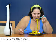 Купить «Large girl eating a measuring tape», фото № 9967896, снято 20 октября 2018 г. (c) PantherMedia / Фотобанк Лори