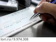 Купить «Firmar un cheque. Sign a bank check», фото № 9974308, снято 28 января 2020 г. (c) PantherMedia / Фотобанк Лори