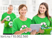 Smiling eco-minded women with tablet and recycling box. Стоковое фото, агентство Wavebreak Media / Фотобанк Лори