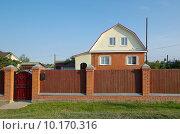 Купить «Кирпичный дом с забором», эксклюзивное фото № 10170316, снято 12 августа 2015 г. (c) Елена Коромыслова / Фотобанк Лори