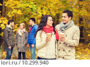 Купить «group of smiling friend with coffee cups in park», фото № 10299940, снято 4 октября 2014 г. (c) Syda Productions / Фотобанк Лори